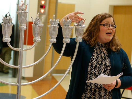 Cantor Elisa Abrams Casuto of Congregation Beth Shalom sings as she lights the first candle on an electric menorah on the opening evening of Hanukkah at Alfred I. duPont Hospital for Children.