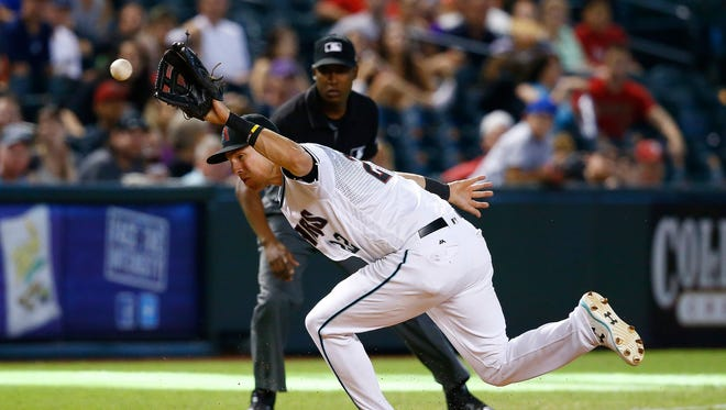 Arizona Diamondbacks' Jake Lamb, left, makes a last second adjustment to get a glove on a grounder hit by Houston Astros' J.D. Davis during the ninth inning of a baseball game Tuesday, Aug. 15, 2017, in Phoenix. Lamb was able to throw to first base for the out. The Astros defeated the Diamondbacks 9-4.