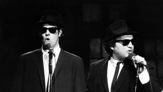 "This Nov. 18, 1978 photo released by NBC shows Dan Aykroyd as Elwood Blues, left, and John Belushi as Jake Blues, performing as the Blues Brothers on ""Saturday Night Live,"" in New York. The long-running sketch comedy series will celebrate their 40th anniversary with a 3-hour special airing Sunday at 8 p.m. EST on NBC."