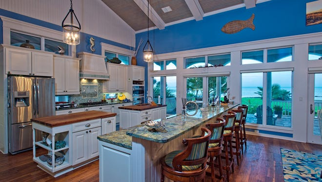 The kitchen is nothing short of perfection with a pair of butcher block topped islands, a large granite topped bar with seating for five; all with breath taking water views and access to the incredible veranda
