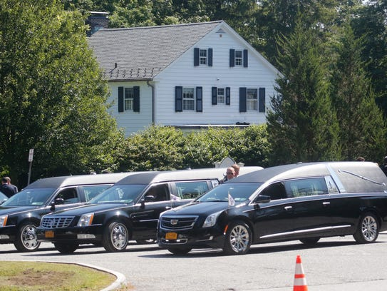 Three hearses parked outside of the Dym funeral Mass