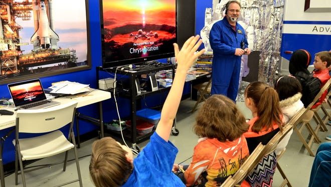 Thomas Ballinger, 12, raises his hand to ask a question about the environment in Mars during a lecture Friday Feb. 13, 2015 at the Challenger Learning Center of Northern Nevada at Sparks High School.