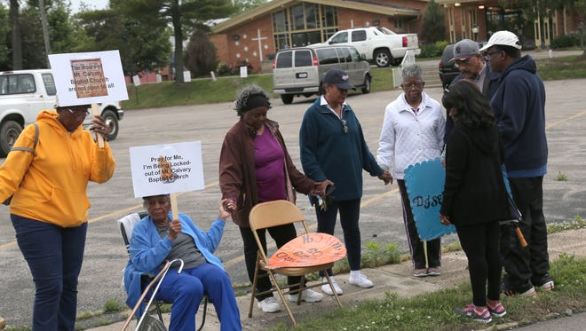 Some of the 22 locked-out members of Mt. Calvary Baptist Church in Mansfield pray before they start protesting outside of the church this past spring. Ejected members and some supporters protested during a church gathering held to celebrate the 2nd anniversary of the Rev. Derek Williams' becoming pastor.