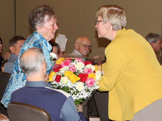 Barbara Frank receives flowers from The Arc of Schuyler Executive Director Jeannette Frank as she is recognized for 23 years of service on The Arc of Schuyler board of directors at the organization's recent annual meeting.