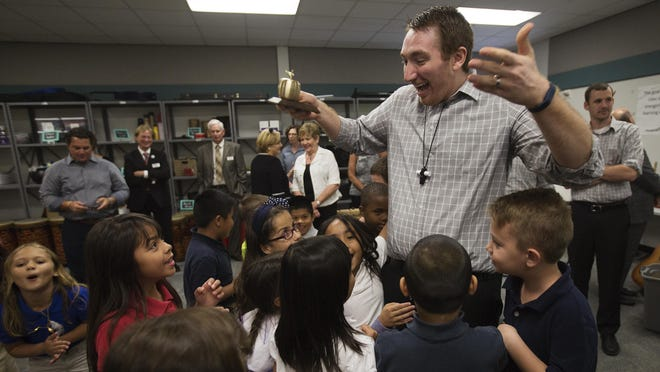 Jason Thomashefsky, a music teacher at Rayma C. Page Elementary School celebrates his Golden Apple moment with students on Friday.