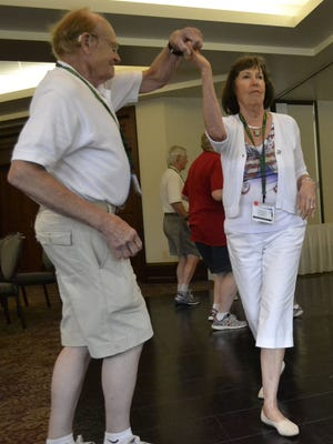 Chuck Foyer leads his wife, Sherry, through a turn as they learn how to do the Hustle in a ballroom-dance lesson during the National Marriage Encounter summer conference at St. Norbert College in De Pere on Saturday, July 12. The Pewaukee couple will be married 55 years Aug. 1.