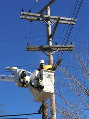A DTE Energy subcontractor works from a crane on March
