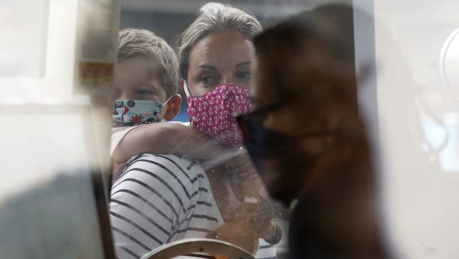 FILE - A woman checks in at the New England Aquarium, Friday, July 17, 2020, in Boston. The Aquarium reopened on Thursday on a reservations only basis after being closed since March due to the coronavirus.
