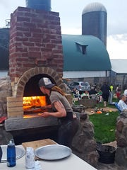 Kat Becker slides a pizza into one of the brick ovens on Stoney Acres farm in Athens.