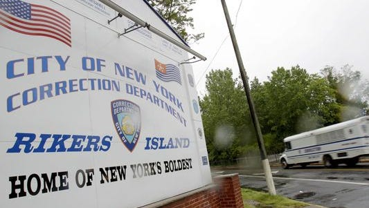 A New York City Department of Corrections bus passes the sign at the entrance to the Rikers Island correction facility in New York.