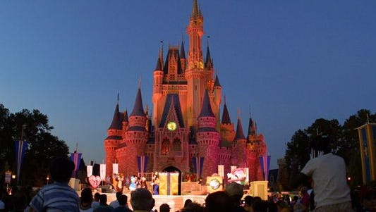 People watch a show on stage in front of Cinderella's castle at Walt Disney World's Magic Kingdom in Orlando, Fla.