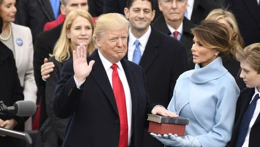 Donald Trump takes the oath of office as the 45th president as his wife, Melania, looks on.