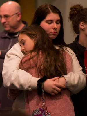 Sisters Kirsten and Johnna Walker embrace at Benton Church of Christ in Benton, Kentucky, following a shooting at Marshall County High School. Two of the churches' members were injured by the shooting, one being left in critical condition. Jan. 23, 2018