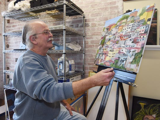 Jeff Aman contemplates one of his paintings in his