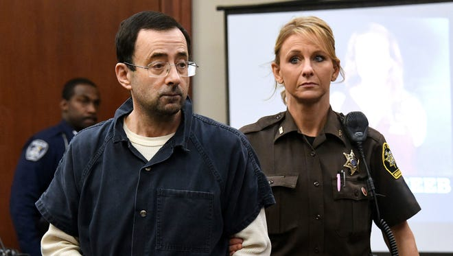 Larry Nassar is pictured being escorted into the courtroom in Lansing, Mich.