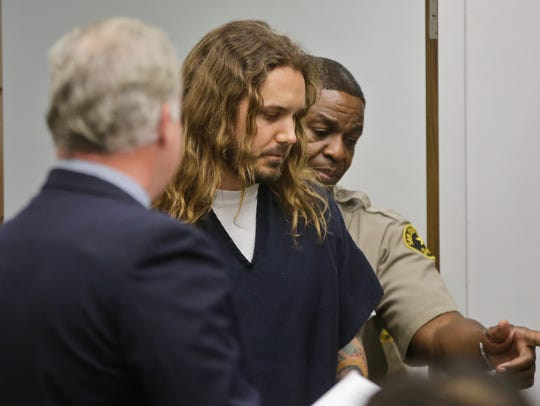 Tim Lambesis, the lead singer for the metal band As I Lay Dying, is escorted by a San Diego sheriff deputy into Superior Court for an arraignment in this file photo.