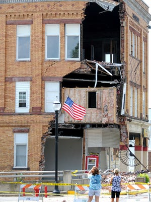 Onlookers take pictures of the crumbling building that housed Napoli's Pizza.