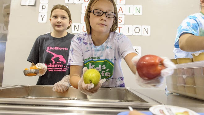 Maddie Heaberlan, left, served carrots while Anna Belle Owen offered students their choice of fruit during the Mitchillville Kids Cafe. Kids Cafe provides free lunches and educational opportunities to children in the SEP district.