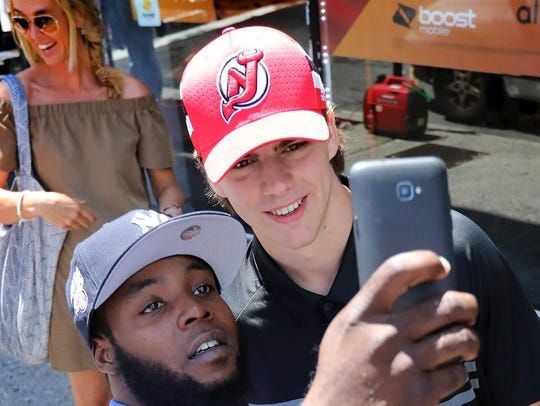 Devils fan,Kahlid Alston takes a selfie with Nico Hischier
