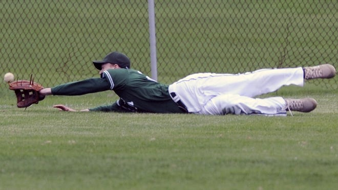 Dennis-Yarmouth left fielder Cam Dennison dives for a drive in a high school game against Sandwich last year.