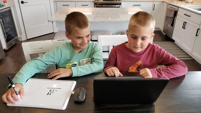 Jack Hartman, left, and his brother Luke, work on their laptop for their virtual learning sessions in Oak Creek, Wisconsin.