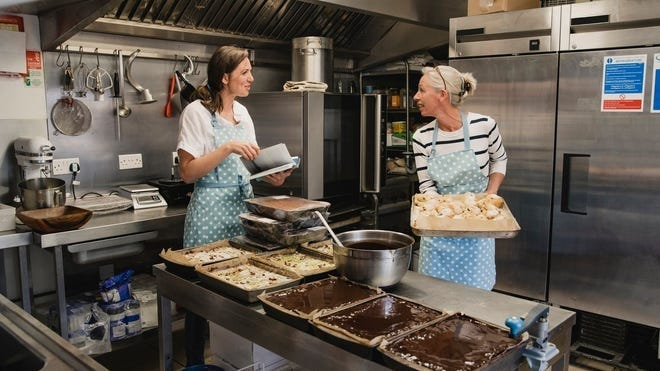 Two women in aprons work in a kitchen with a cart of baked goods
