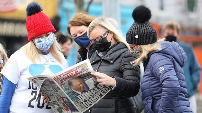 Residents read a copy of their local paper in the town of Ballina, North West of Ireland, the ancestral home of President elect Joe Biden, Saturday, Nov. 7, 2020. Biden was elected Saturday as the 46th president of the United States, defeating President Donald Trump in an election that played out against the backdrop of a pandemic, its economic fallout and a national reckoning on racism.  Peter Morrison, AP