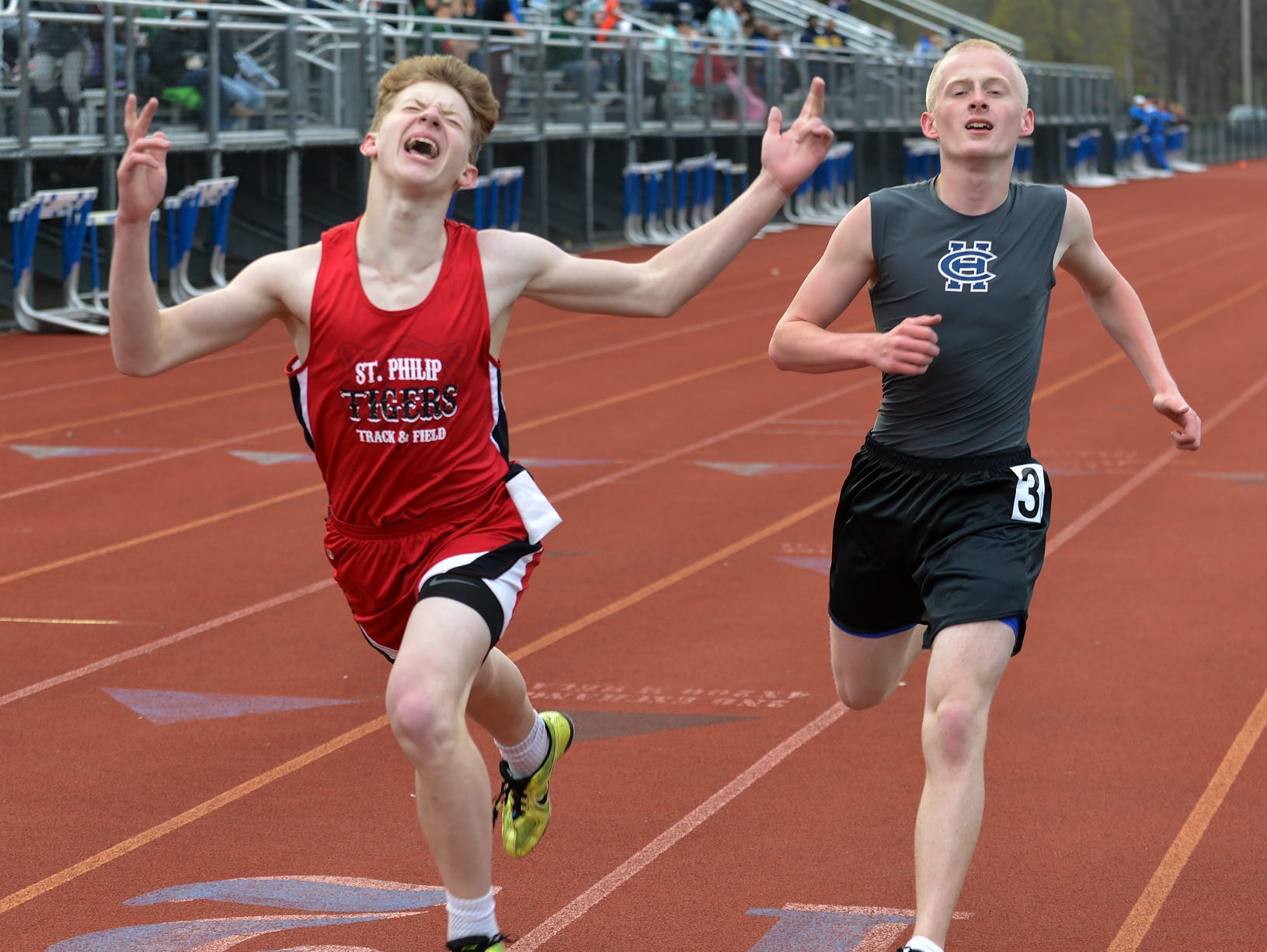 St. Philip's Kenny Wojcik lunges for the finish line as he passes Harper Creek's Devon Funk for second place in the 1600 meter run during the 2016 All City Track Meet held at Harper Creek High School Friday afternoon.
