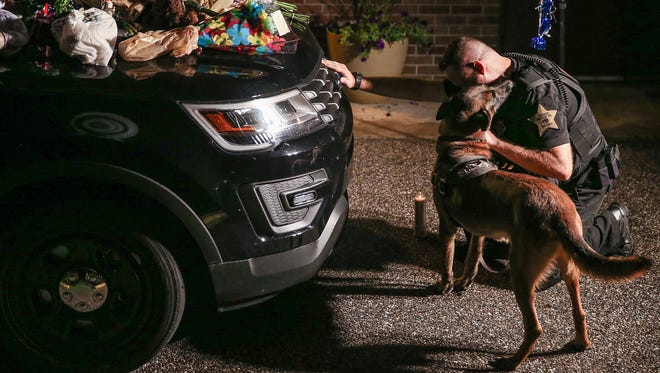 Marion County Sheriff James Essex and K-9 Eik kneel in prayer in front of late Southport Lt. Aaron Allan's car at the Southport Police Department, Indianapolis, late into the evening, Thursday, July 27, 2017. Allan died at Eskenazi Hospital after being shot during a call to a vehicle crash on the city's south side. Essex grew up only a few blocks away from the Southport department and considers Southport his home. He had previously worked with Allan in Marion County.