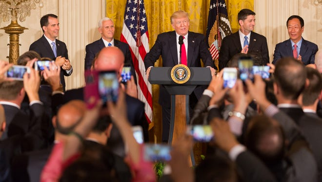 President Donald J. Trump (center) delivers remarks during the Jobs Announcement event with Foxconn  Wednesday, July 26, 2017, in the East Room of the White House in Washington, D.C. With him (from left) Wisconsin Governor Scott Walker, is Vice President Mike Pence , U..S. Representative Paul Ryan, and Foxconn Technology Group Chairman Terry Gou. (Official White House Photo by Shealah Craighead)