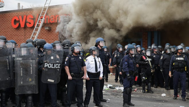 Baltimore Police form a perimeter around a CVS pharmacy that was looted and burned near the corner of Pennsylvania and North avenues during violent protests following the funeral of Freddie Gray April 27, 2015 in Baltimore.