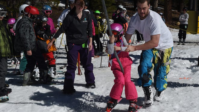 Volunteer Brent Klitzke, right, helps a new skier load the poma lift during opening day at Sky Tavern ski area just outside of Reno on Feb. 14, 2015.