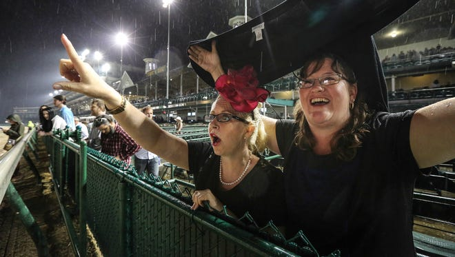 "Karrie Rossmiller, left, and friend Shannon Cooper watch their horses from the rail.  ""The rain's not gonna dampen our fun!"" says Rossmiller. This is Rossmiller's third opening day/night and Cooper's first."