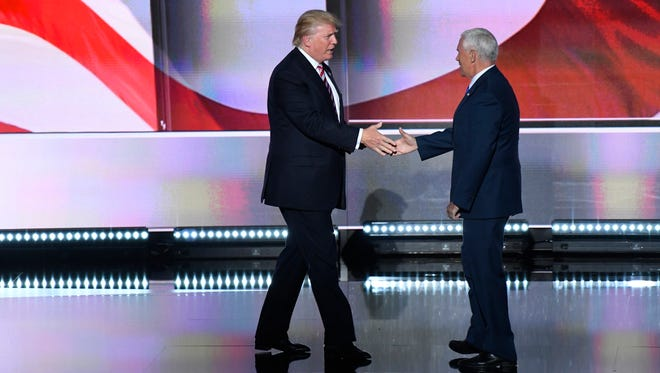 Donald Trump shakes hands with Mike Pence after Pence addressed the audience during the Republican National Convention on July 20, 2016.