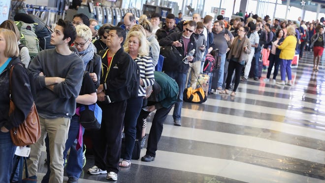 Passengers at O'Hare International Airport wait in line.