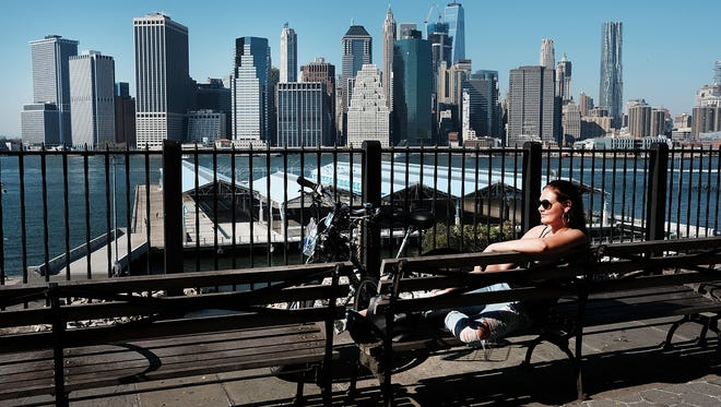 A woman sits in the sun on a summerlike day on Oct. 18, 2016, in the Brooklyn borough of New York City. New York and much of the East Coast are experiencing an Indian summer as temperatures reach into the high 70s.