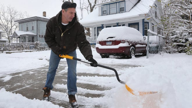 In this Friday, Dec. 9, 2016 photo, T.J. Seiwert clears snow in the Vine neighborhood of Kalamazoo after few more inches of snow fell overnight and in the morning.