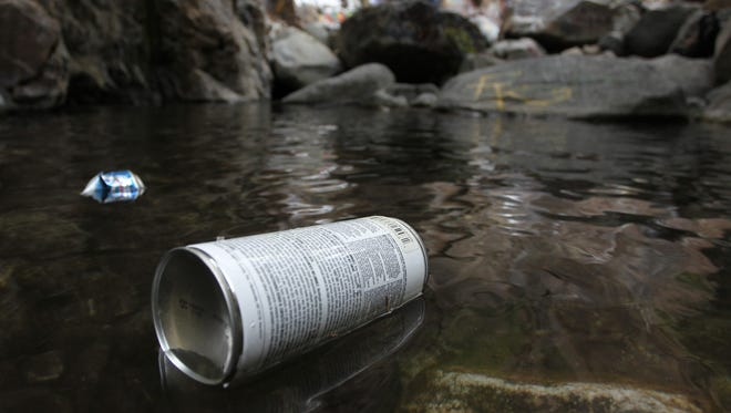 RANCHO CUCAMONGA, CA —  A paint can floats down a creek from the spot where vandals had just spray painted rocks near Sapphire Falls in Cucamonga Canyon on June 23, 2013 in the Angeles National Forest near Rancho Cucamonga, California.