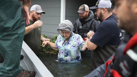 Volunteer rescuer workers help a woman from her home that was inundated with the flooding of Hurricane Harvey on Aug. 30, 2017 in Port Arthur, TX.