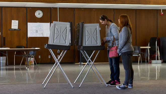 Colleen Elliott votes while her daughter, Emily Elliott, 12, stands next to her at the Warren Woods Education Center on Tuesday, Nov. 7, 2017 in Warren.