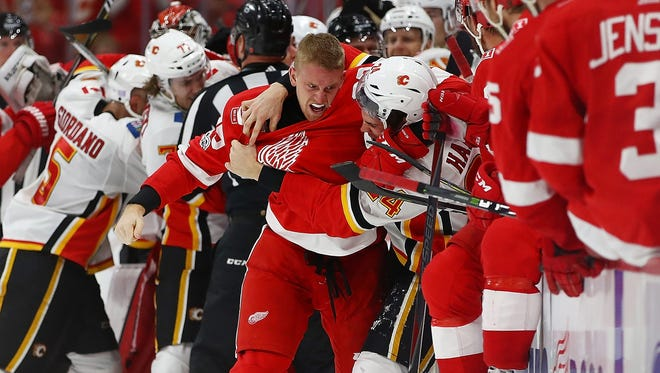 Anthony Mantha of the Detroit Red Wings gets in a fight with Travis Hamonic of the Calgary Flames during the third period Wednesday night.