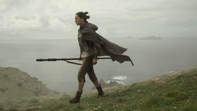 """Rey (Daisy Ridley) walking along mountain of Ahch-To trains to become Jedi in """"Star Wars: The Last Jedi."""""""