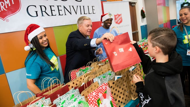 Sen. Lindsey Graham hands out winter clothing gift bags to children during the annual Molina Healthcare of South Carolina Holiday Party at the Kroc Center on Friday, Dec. 15, 2017.