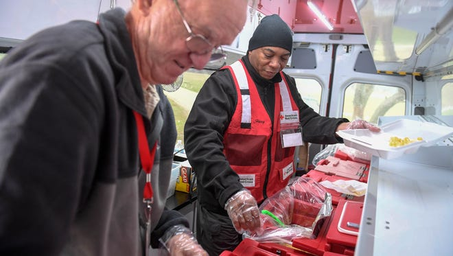 Red Cross volunteers Ray Desrosiers (left) and Ferdale Huey serve up meals to people in need after the Ohio River flooding affected the Tri-State in February.
