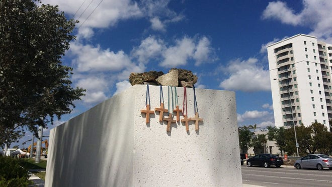 Six crosses are placed at a makeshift memorial on the Florida International University campus in Miami on March 17, 2018, near the scene of a pedestrian bridge collapse that killed six people on March 15. (AP Photo/Jennifer Kay) ORG XMIT: FLJK101
