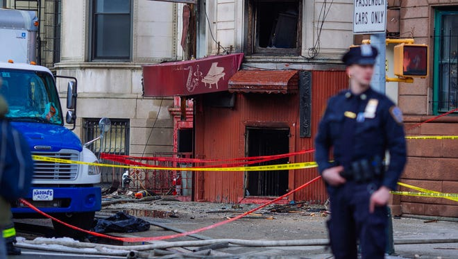An police officer keeps watch outside a burned out building, the scene of a overnight fatal fire on Friday, March 23, 2018, in New York.