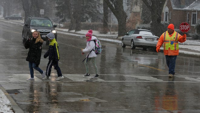 Crossing Guard Richard McDougal ushers students from Webster Stanley Elementary School across Bowen Street at East Melvin Avenue on Tuesday, April 3, 2018. The Oshkosh area was under a winter storm warning until 4 a.m. Wednesday, though it had received only a dusting of snow as of Tuesday afternoon.