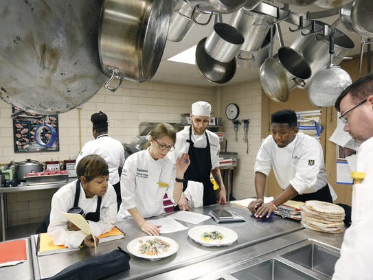 Abby Riley listens to chef Evelyn Lannak as students