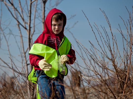 Volunteer David Smith, 7, of Port Huron, picks up cigarette butts along with his family Saturday, April 18, 2015 along the Blue Water River Walk in Port Huron.