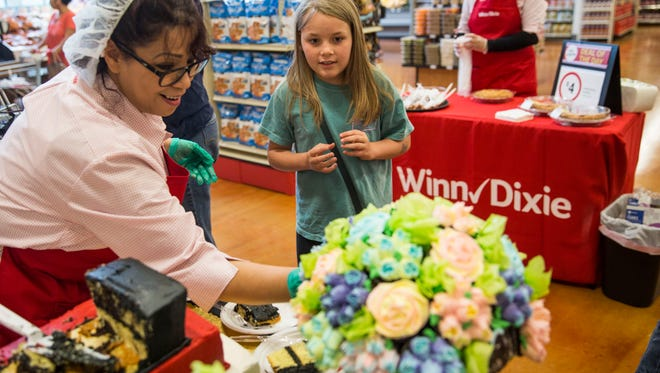 Julie Brooks, 10, waits for a flower cupcake at the Winn-Dixie grand reopening on Wednesday, May 16, 2018.